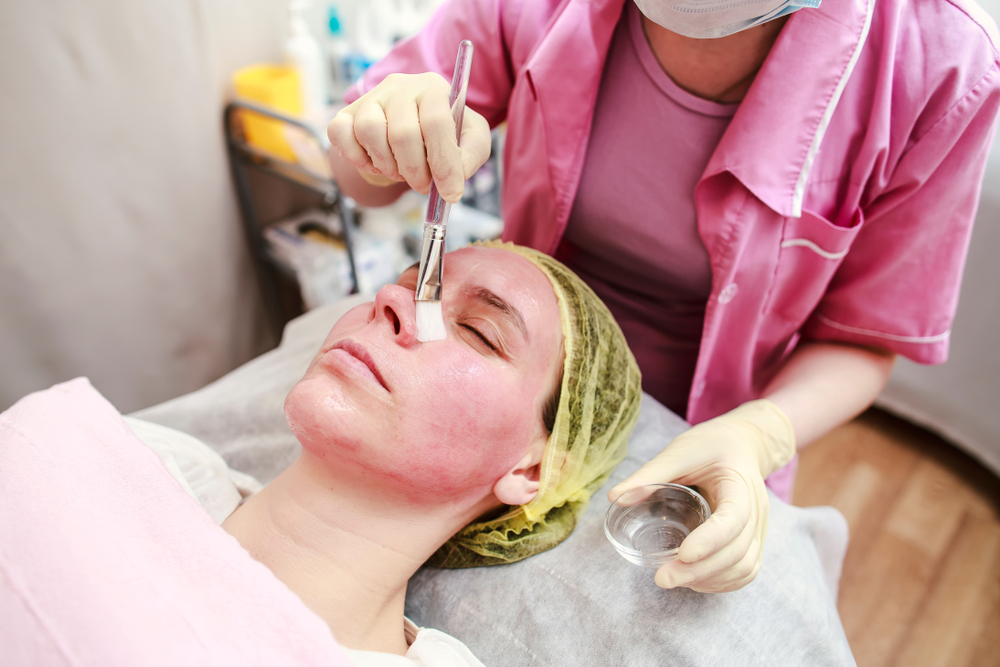 Clinician applying chemical peel to treat acne