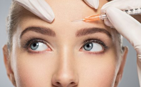 aesthetician administering botox injections in patients forehead