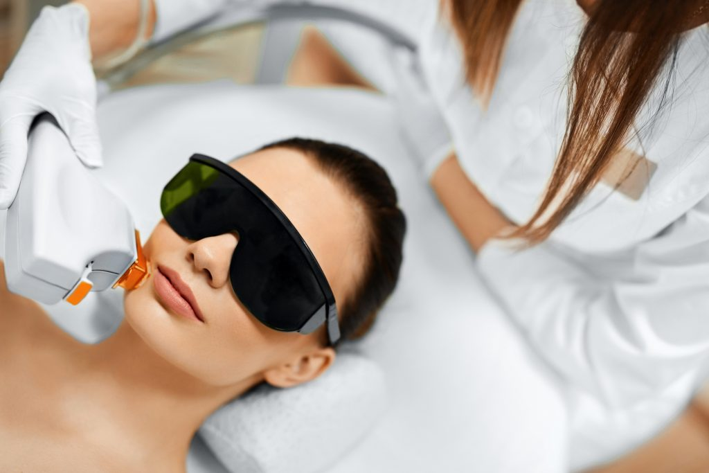 Clinician performing an IPL photorejuvenation facial to treat skin redness.