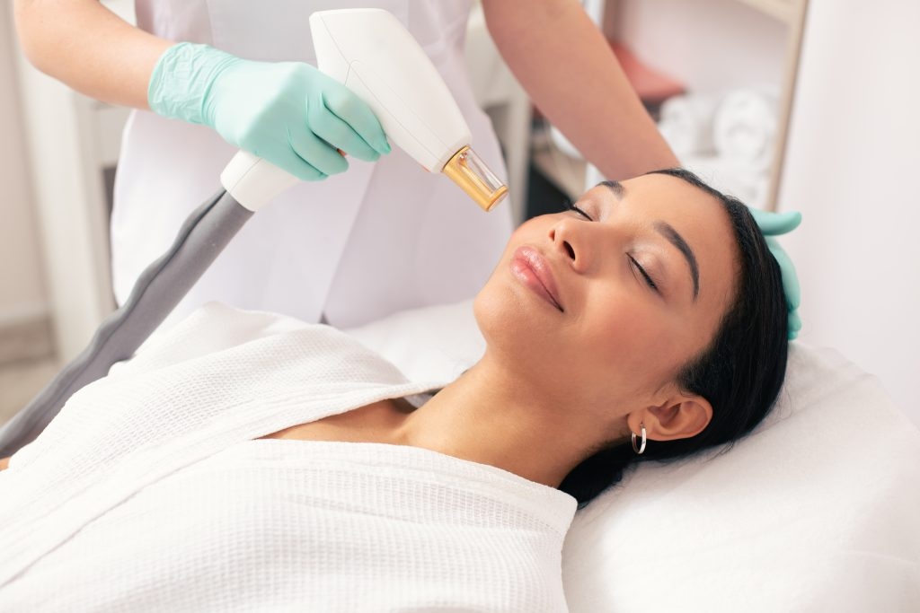 Aesthetician using a ND-YAG laser to perform a laser lift and plump facial