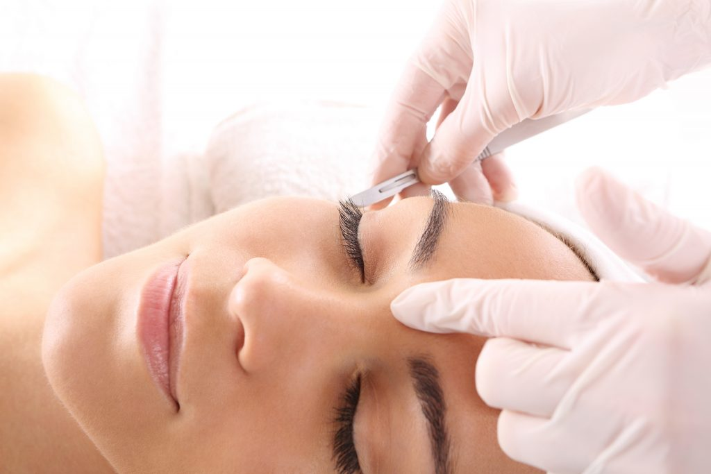 Aesthetician exfoliating clients skin with a dermaplaning facial